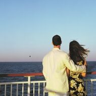 Couple on cruise ship looking at ocean, sunset, rear view  200129496-001